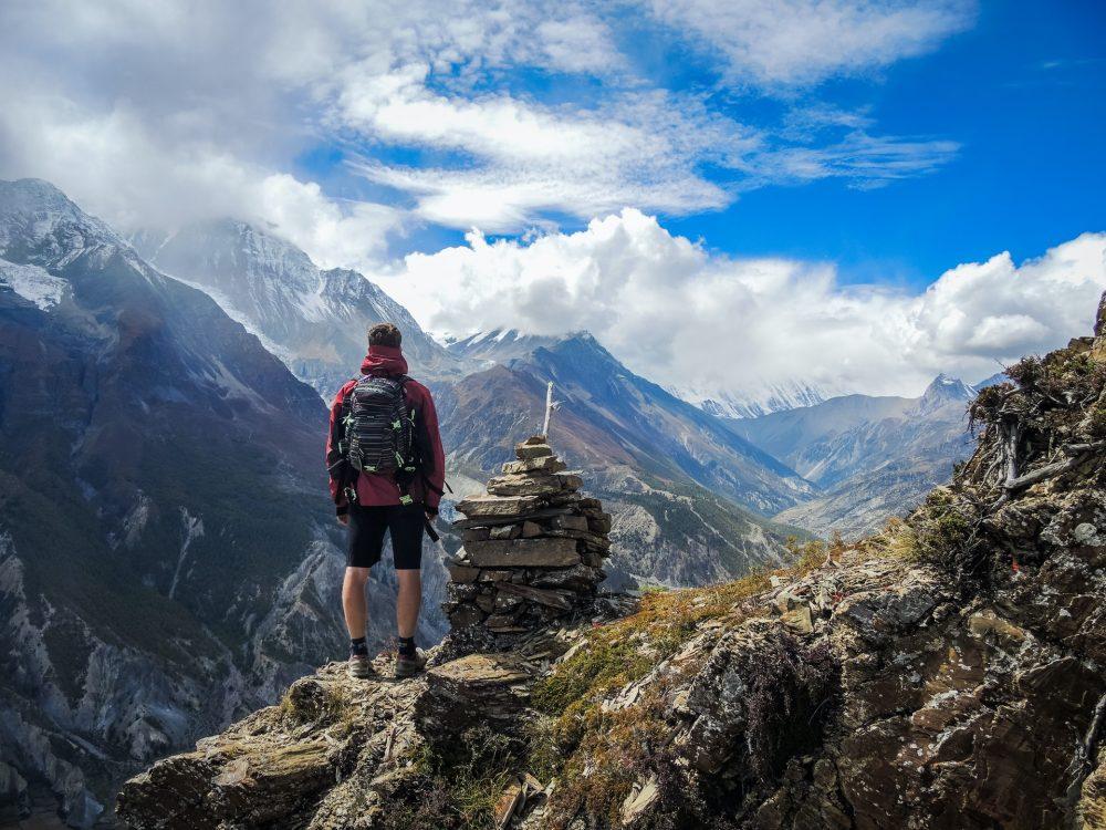 Homme debout au sommet d'une montagne portant un sac à dos randonnée 20L