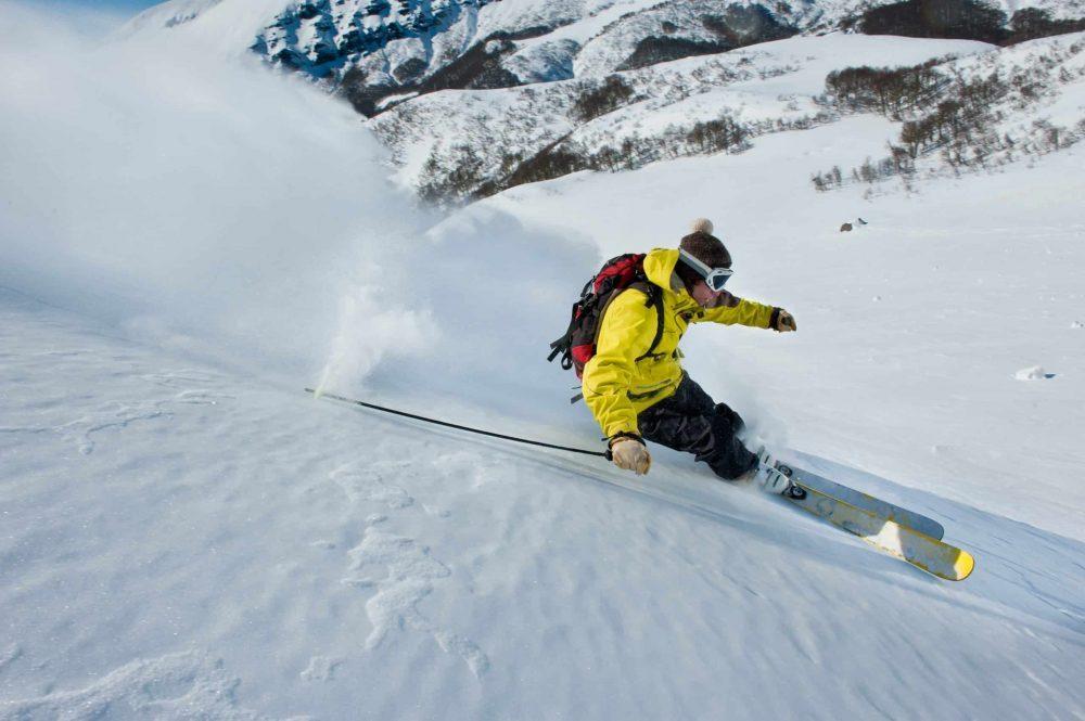 Skieur dérapant dans la neige en dehors des pistes