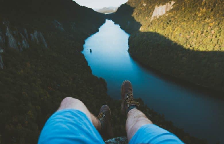 homme assi dans le vide surplombant une rivière
