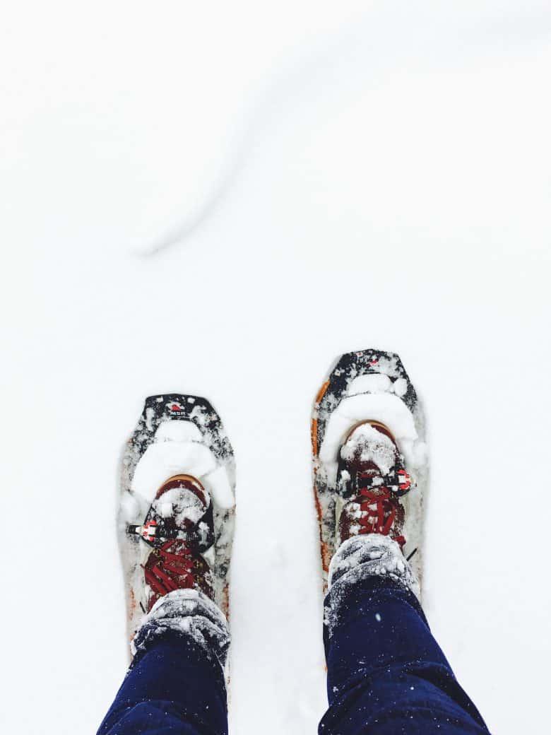Une personne debout portant des raquettes à neige