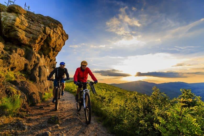 Femme et homme sur un VTT, cadre alu, cadre carbone au coucher du soleil