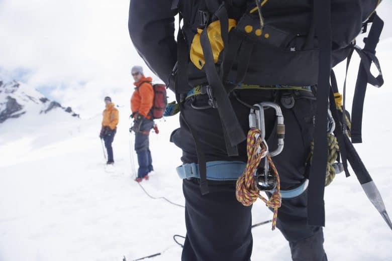 Vue arrière d'un randonneur avec sac à dos et corde de sécurité