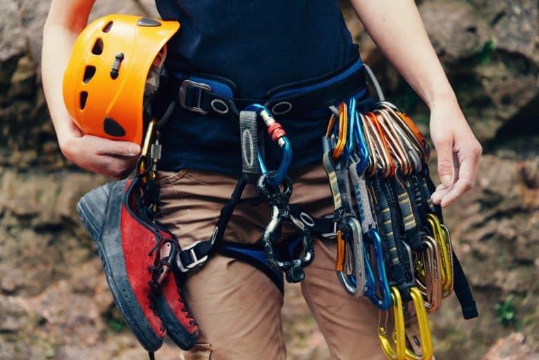 Femme debout avec un équipement d'escalade et un casque