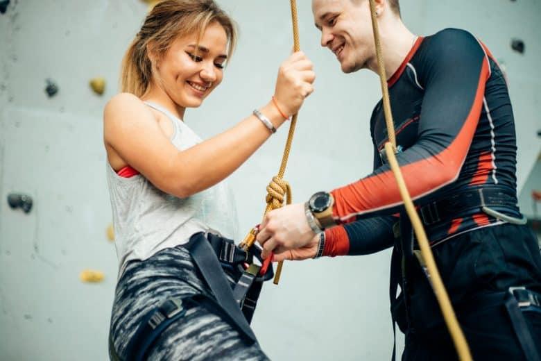 Entraîneur tapant le harnais d'une femme sur un mur d'escalade dans un gymnase