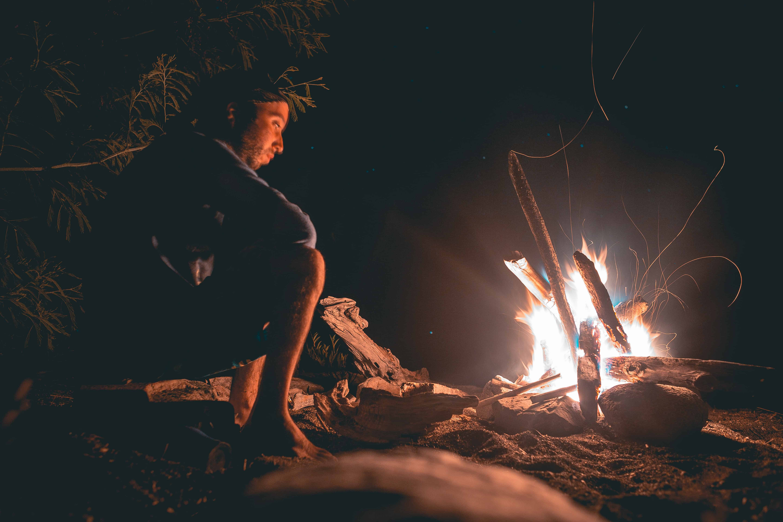 homme près d'un feu de campement