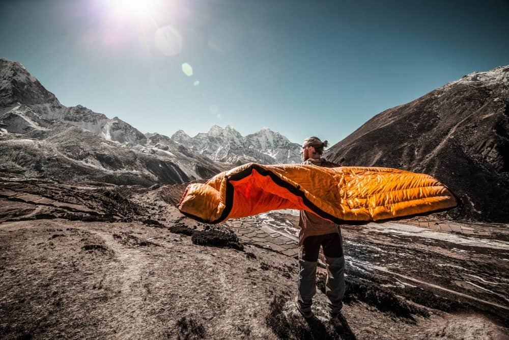 homme avec sac de couchage orange