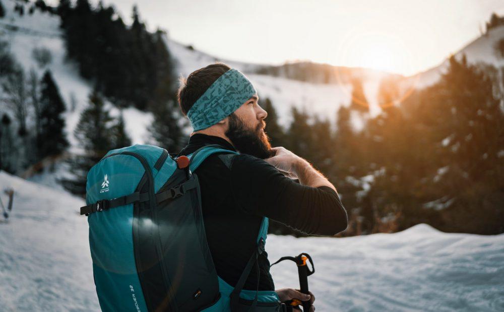 Un homme débout portant un sac à dos ski de randonnée