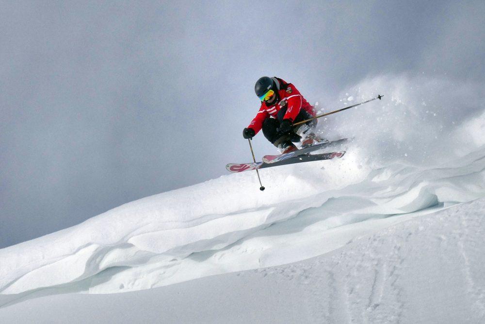 homme portant un casque de ski en descente