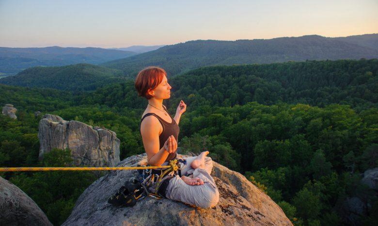 Jeune fille athlétique progressant en escalade, assise et sécurisée par une corde, en train de méditer.