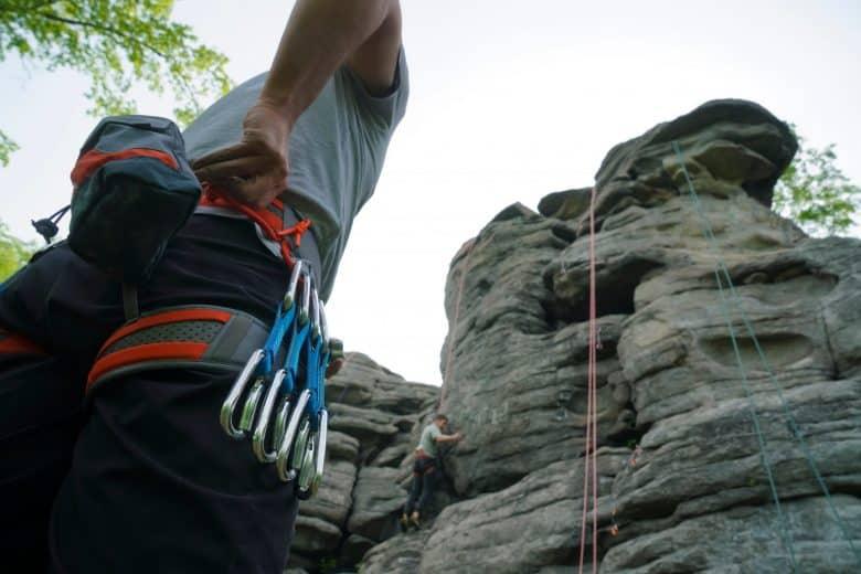 Homme avec son harnais et son équipement d'escalade à la ceinture qui progresse en escalade