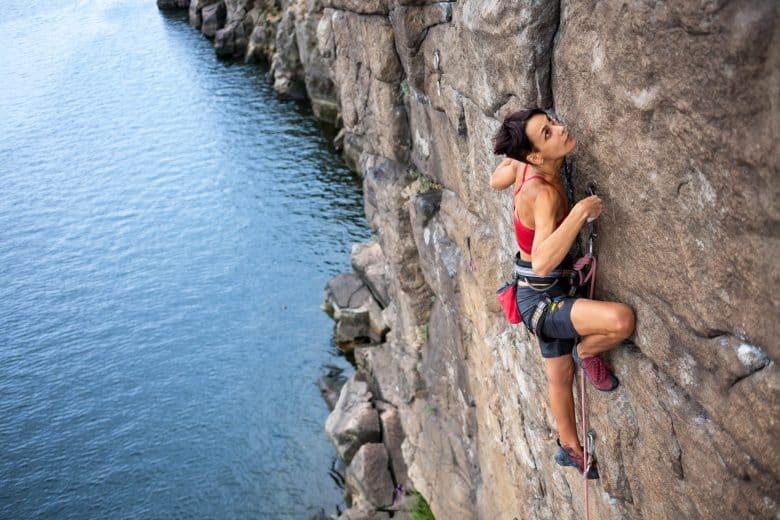 Une fille progressant en escalade d'une voie d'escalade au-dessus de l'eau.