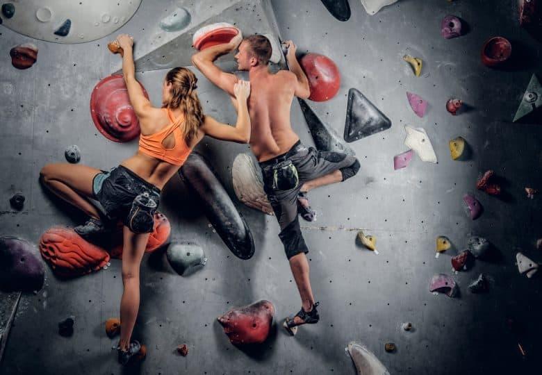 Homme et femme sportifs progressant en escalade sur un mur