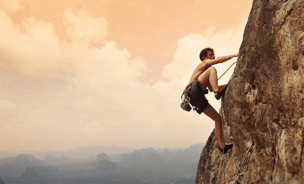 Jeune homme grimpant sur une paroi calcaire avec une large vallée