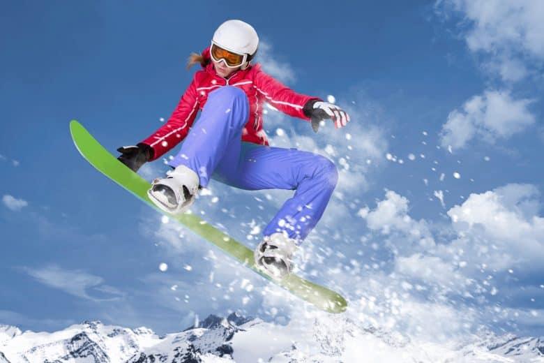 Un snowboarder en veste rouge qui saute