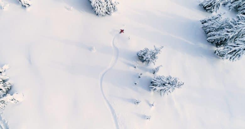Un snowboarder à l'angle d'un drone tourne dans la poudreuse d'une montagne