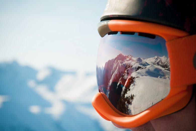 Une chaîne de montagnes qui se reflète dans le masque de ski