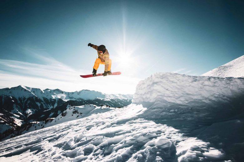 Un snowboarder saisit sa planche dans les airs