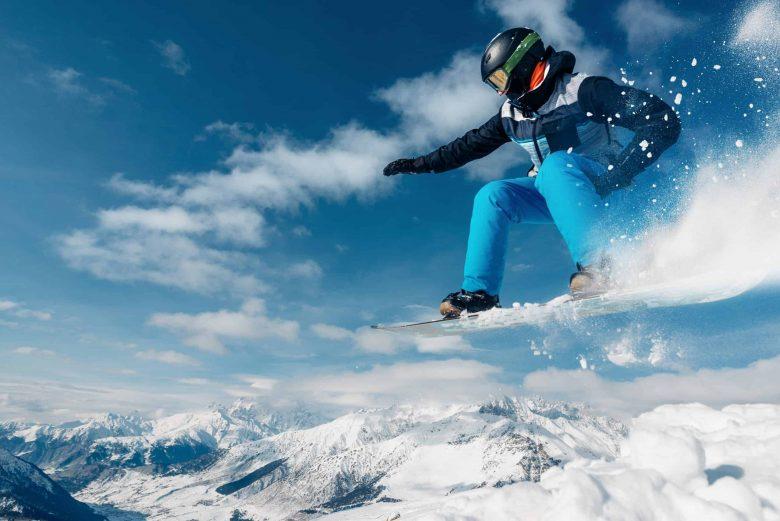 Un snowboarder saute avec son snowboard depuis une colline très haute