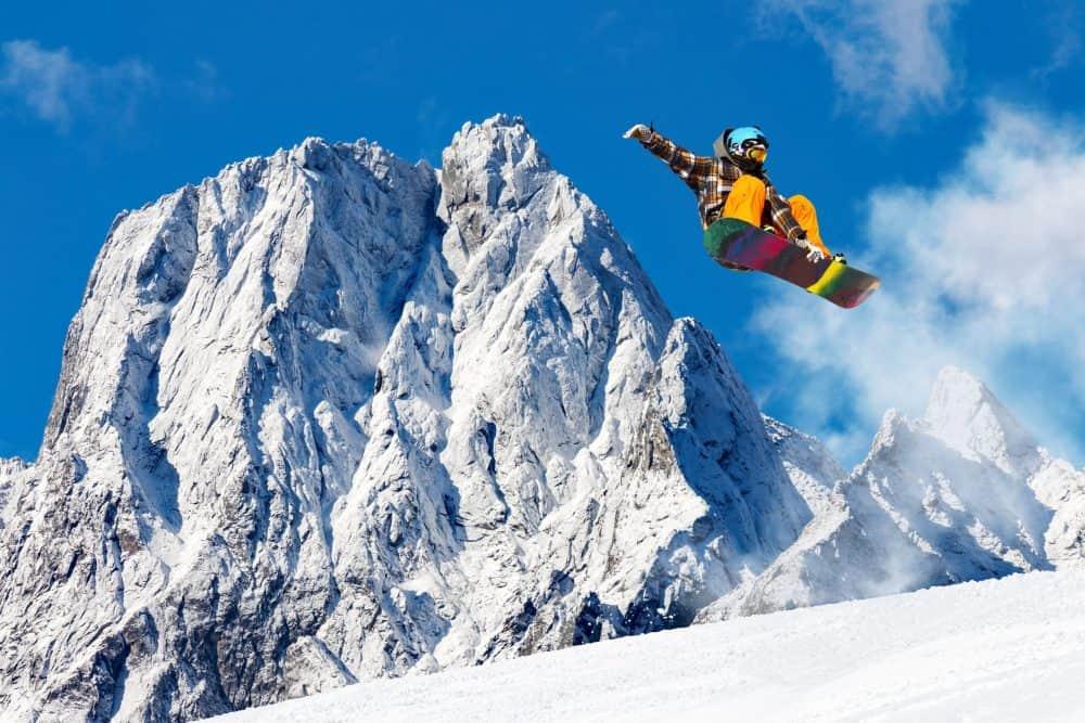 Saut de snowboard dans un paysage alpin