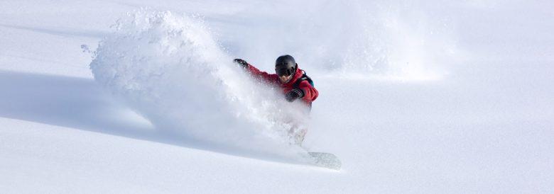 Un freerider en combinaison lumineuse fait de l'héliski et du snowboard