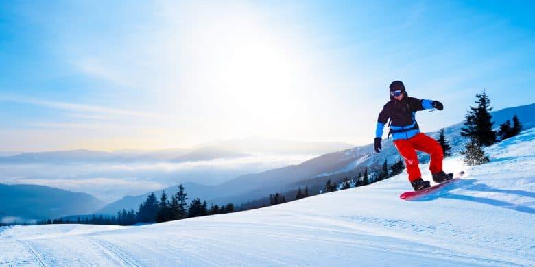 Snowboarder faisant du snowboard rouge dans les montagnes par une journée ensoleillée.