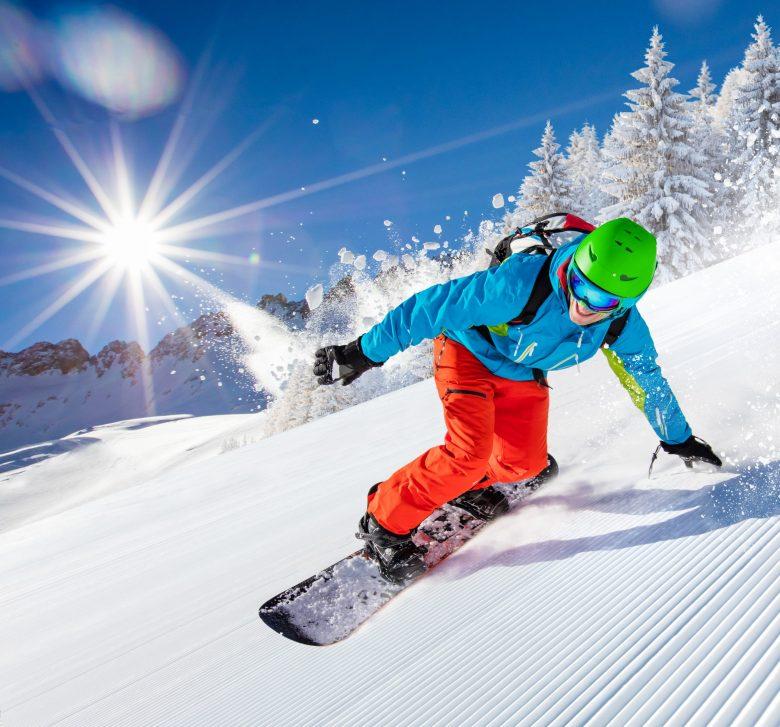 Homme actif faisant du snowboard sur une pente par une belle journée ensoleillée.