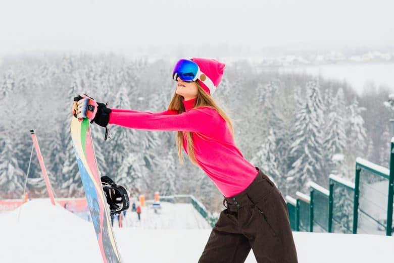 Une jeune fille heureuse qui fait du snowboard et qui pose avec des lunettes de soleil