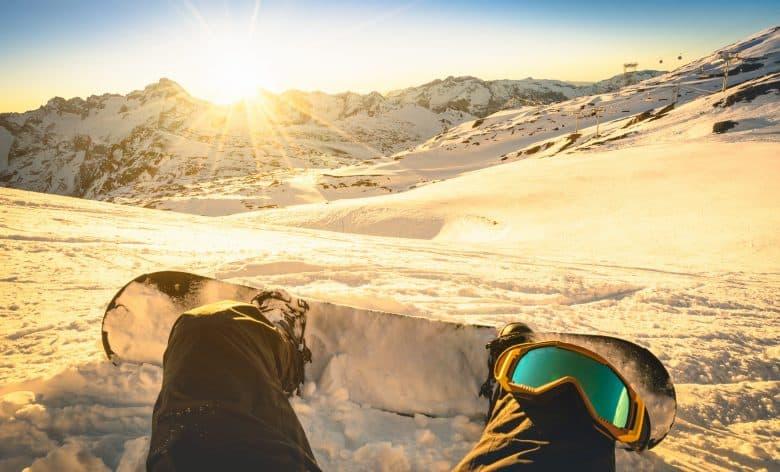Snowboarder assis sur un moment de détente au coucher du soleil dans les Alpes françaises