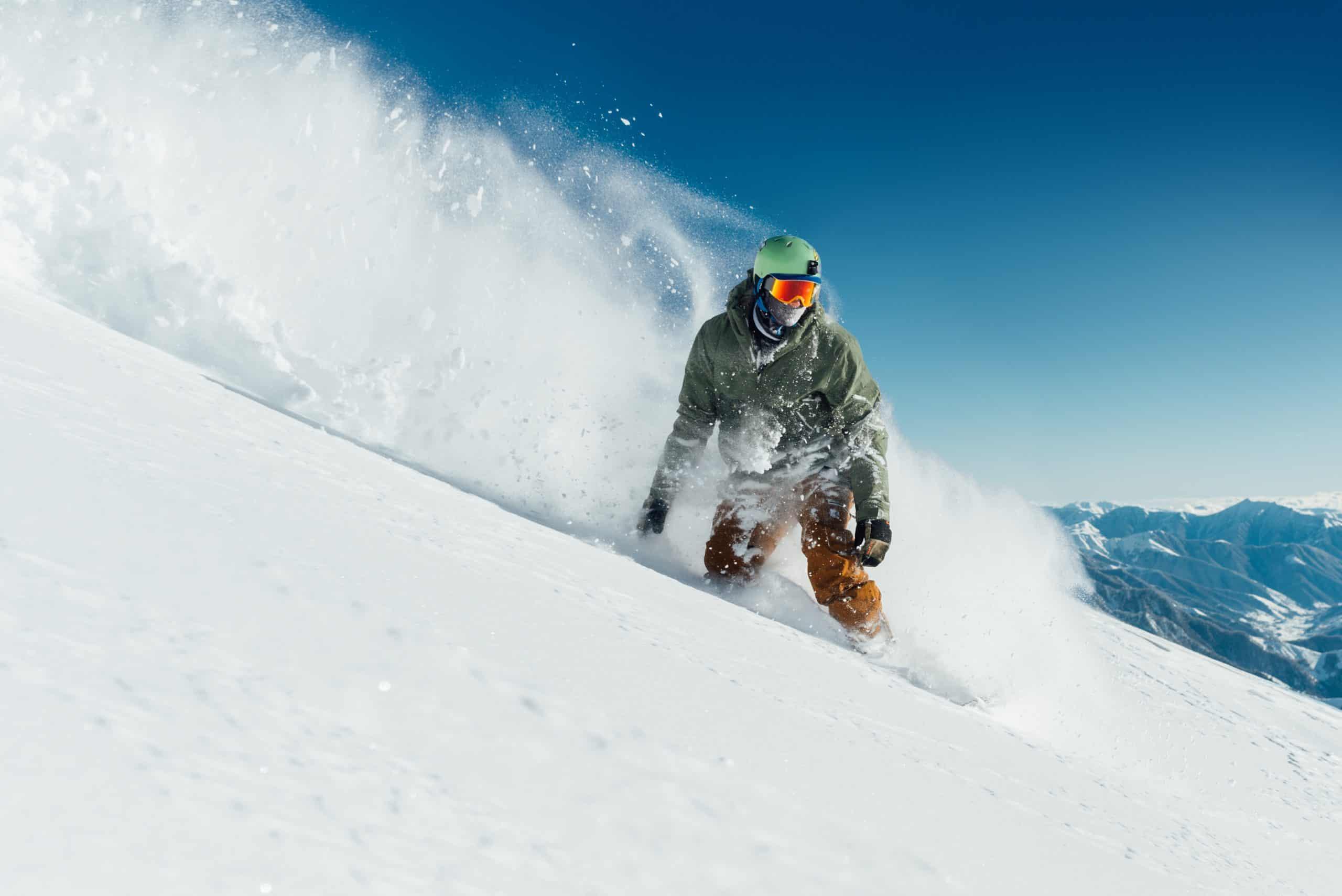 Un snowboarder masculin courbe et freine en pulvérisant de la neige profonde