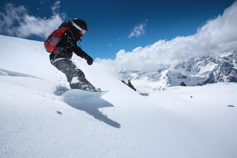 Jeune femme en train de faire du snowboard dans la neige profonde
