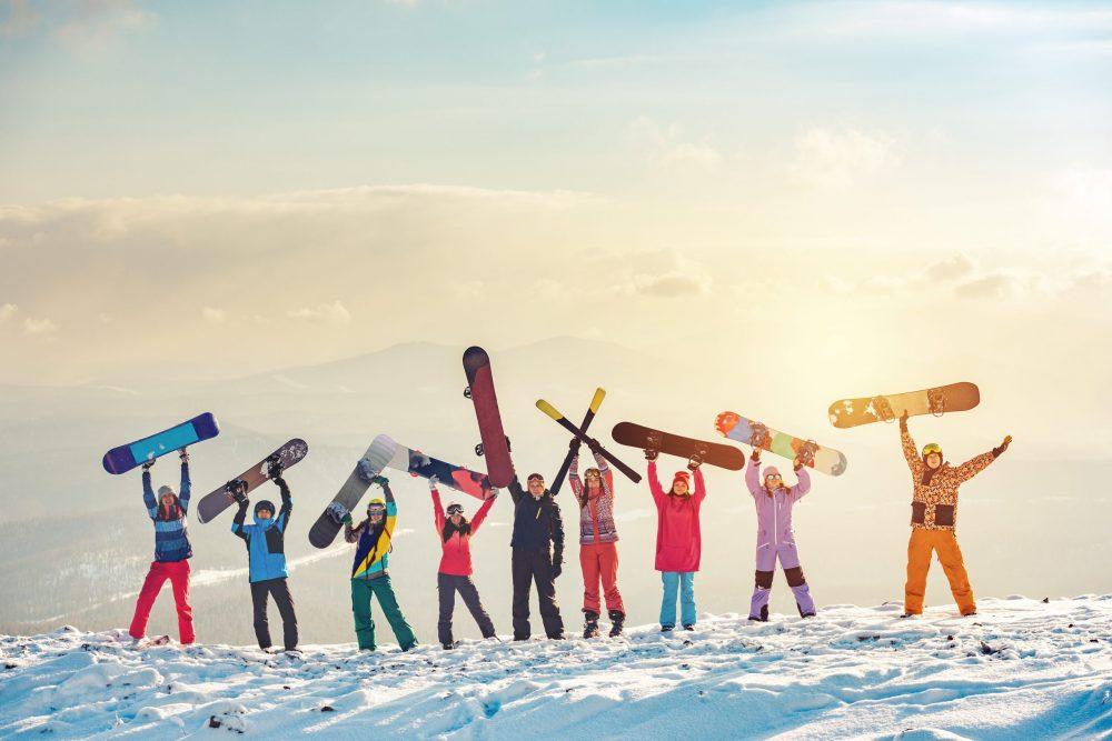 Groupe d'amis heureux, skieurs et snowboarders s'amusant